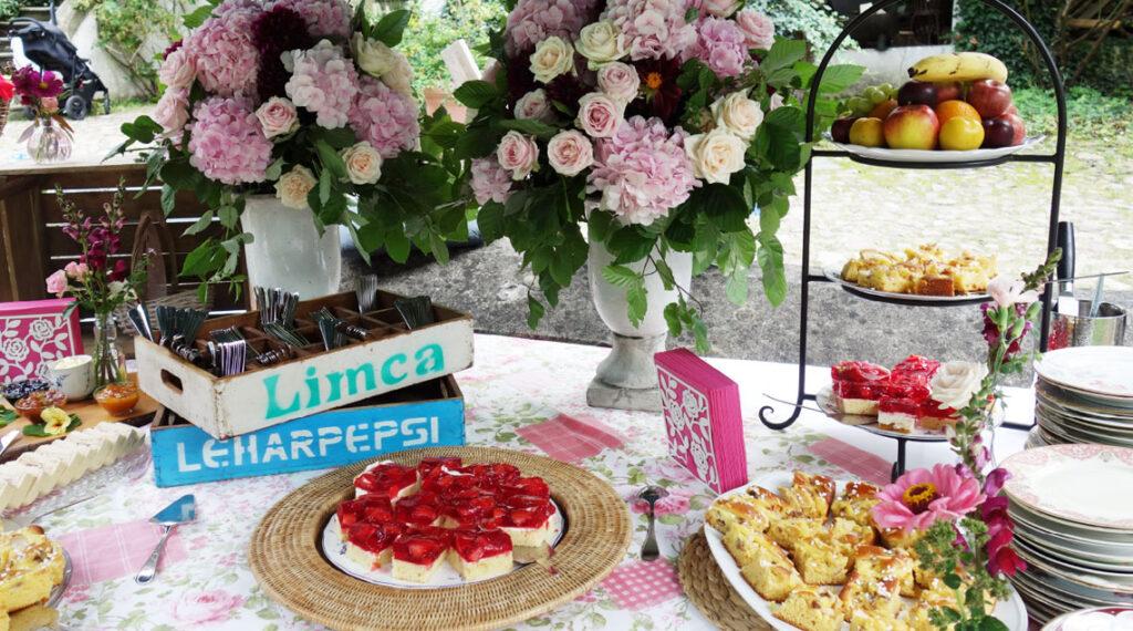 Kuchenbuffet mit üppiger Blumendekoration im Garten des Schloss Blankensee
