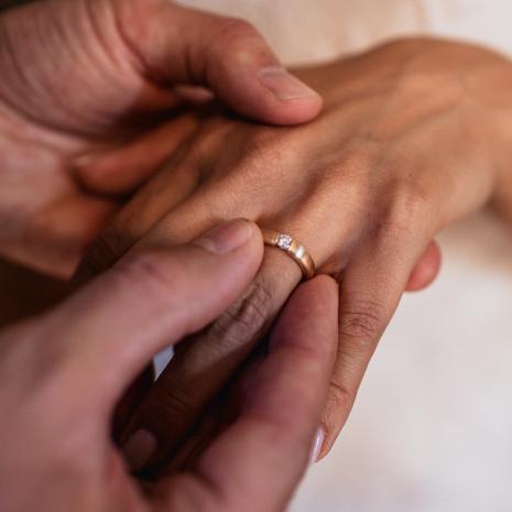 Der Ehering wird der Braut auf den Ringfinger geschobent
