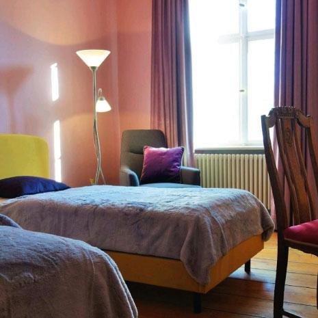 zimmer mit gemütlichem Bett und antiken Stuhl
