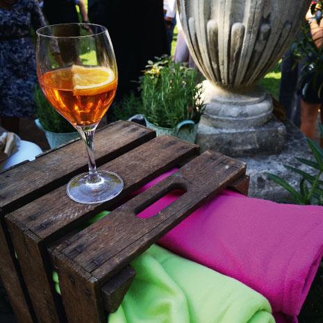 Holzkiste mit farbigen Decken – auf der Kiste steht ein Glas Prosecco
