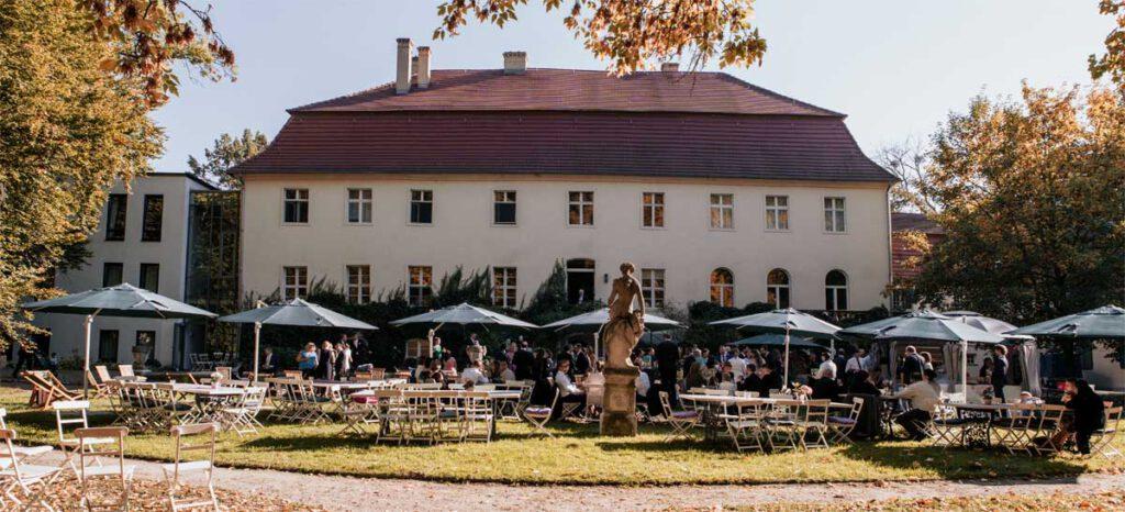 Blick auf das Haus und arrangiertem Garten für Feierlichkeit mit Sonnenschirmen und gedeckten Tischen