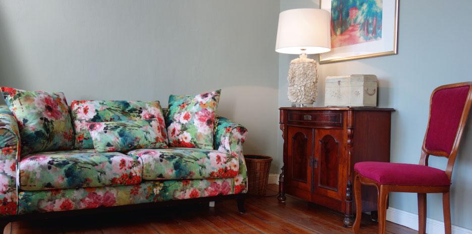 geblümtes Sofa und antike Anrichte