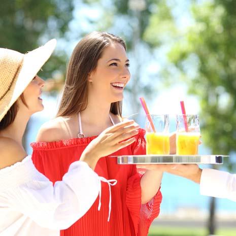 zwei Frauen bekommen bei Sommerfeier Getränke gereicht