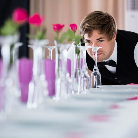 Kellner überprüft die Tisch-Dekoration